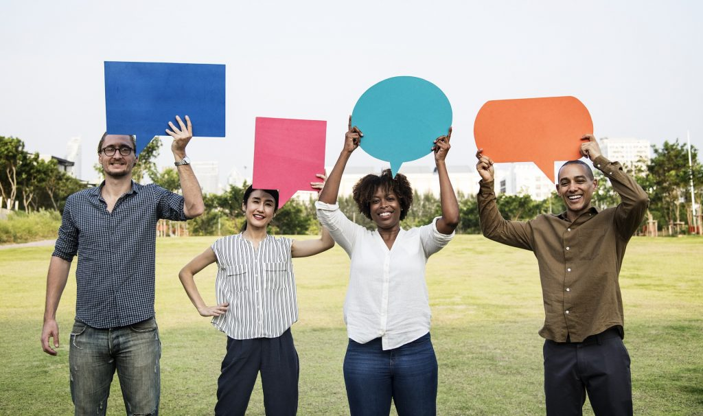 A row of four people holding blank speech bubbles above their heads